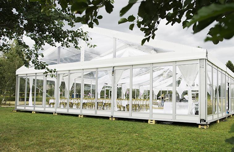 Ett stort tält mitt i naturen som kund hyrt till sitt bröllop