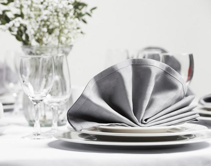 en dukning med porslin, bestick, glas och servetter på ett bord