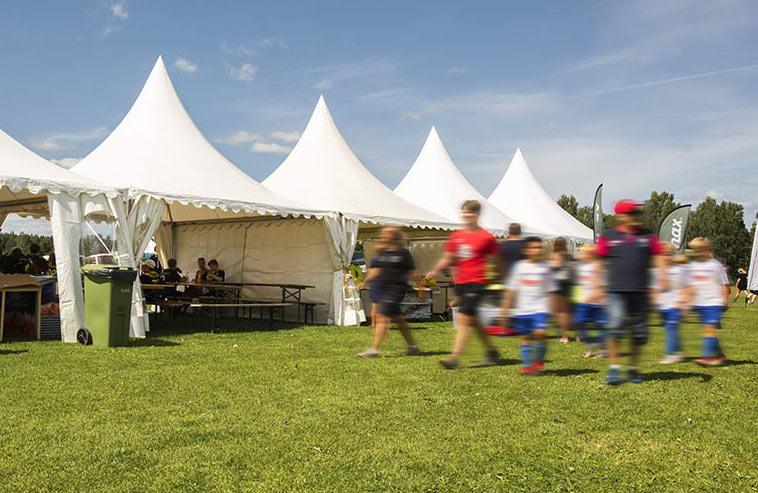 Små hyrtält på en fotbollscup, fotbollslag går förbi.