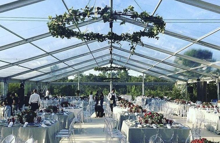 Ett mellanstort tält med transparent tak och glasvägga på ett bröllop.
