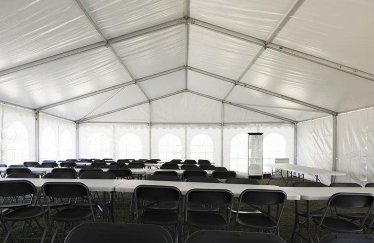 Ett hyrtält, bord och stol monterat åt ett företag som ska ha företagsfest.