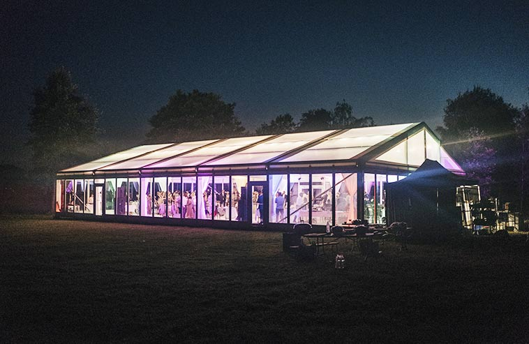 Ett bröllopstält som kund hyrt, med transparent tak och glasväggar som lyser på kvällen.