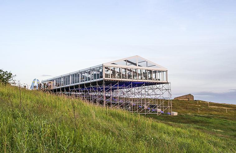 Ett eventtält med byggställningar mitt på en kulle.