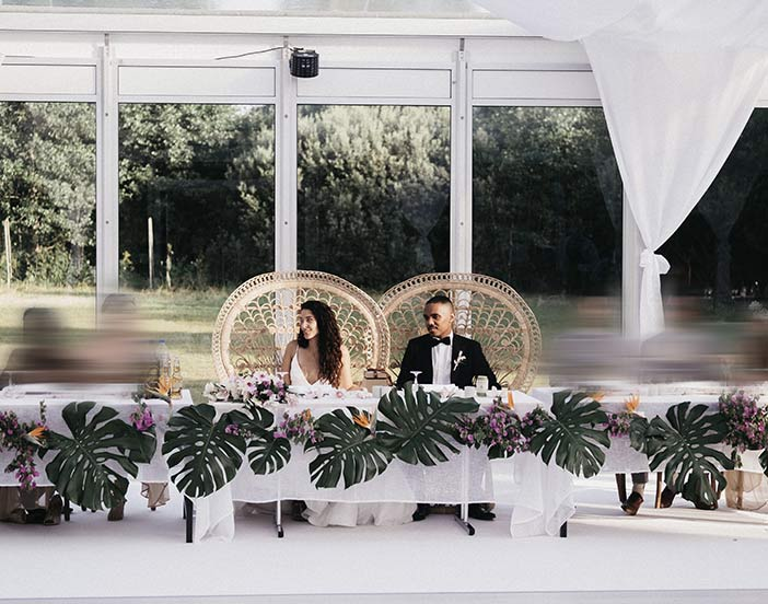 Brudpar vid honnörsbordet inuti ett hyrt bröllopstält.